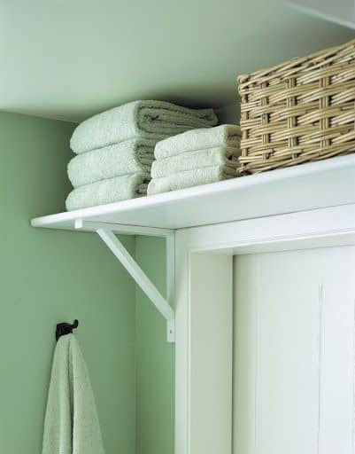 A shelf above the bathroom door provides added storage.