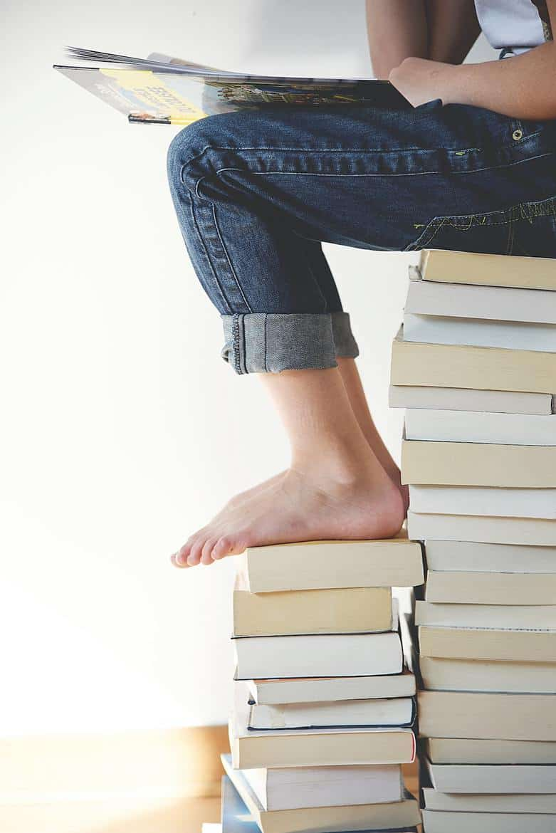 child sitting on stack of books