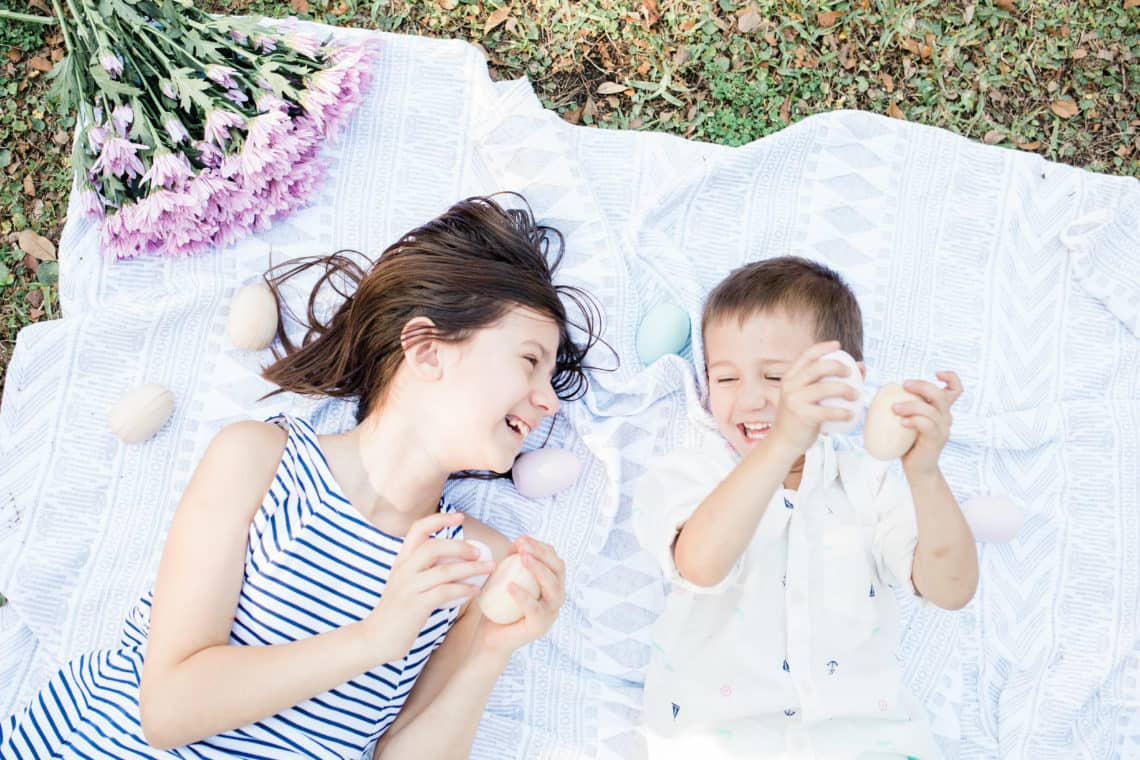 Young children playing with easter eggs on a blanket featuring kids easter outfits they will wear again