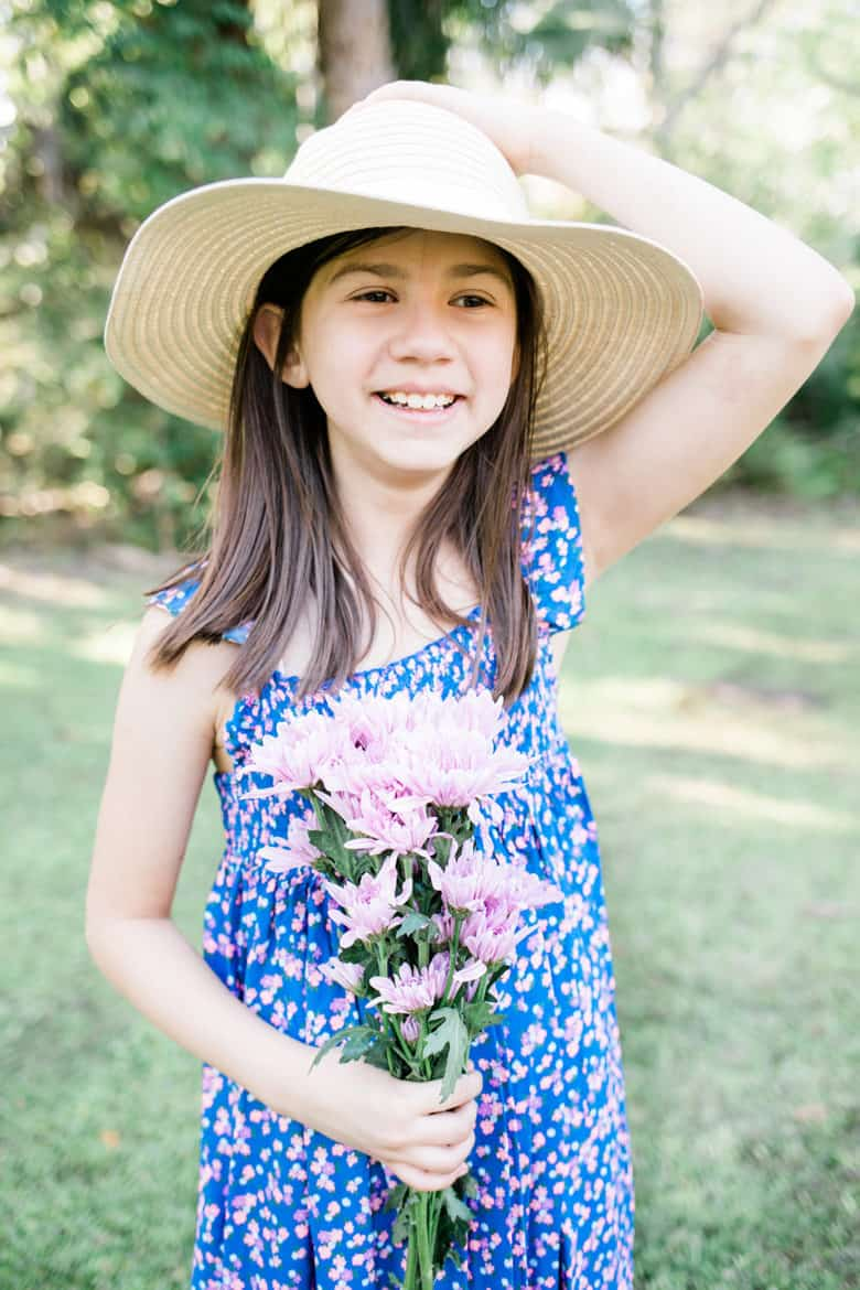 A young girl holds flowers wearing a long flowing kids easter outfits dress.