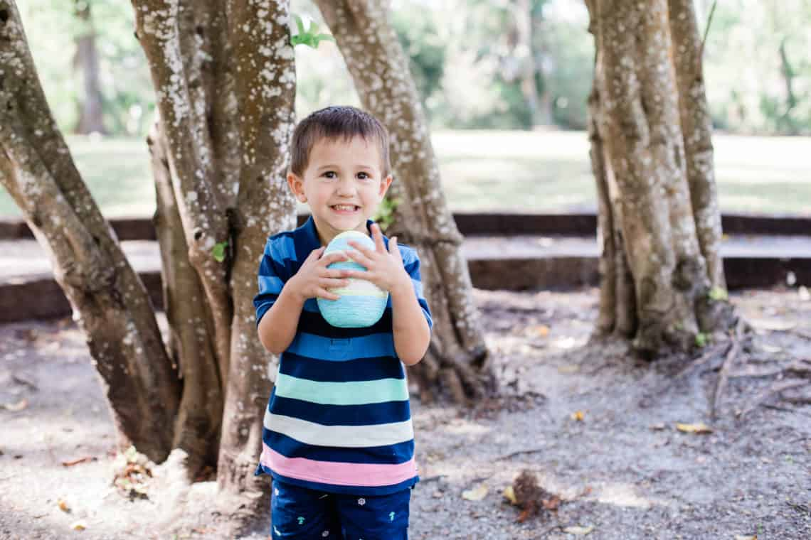 Toddler boy carries an easter egg wearing kids easter outfit striped polo and shorts