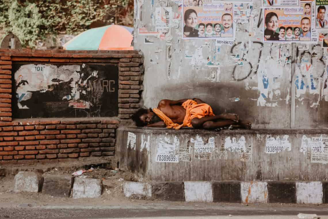 A poor homeless man sleeps by a temple india 2