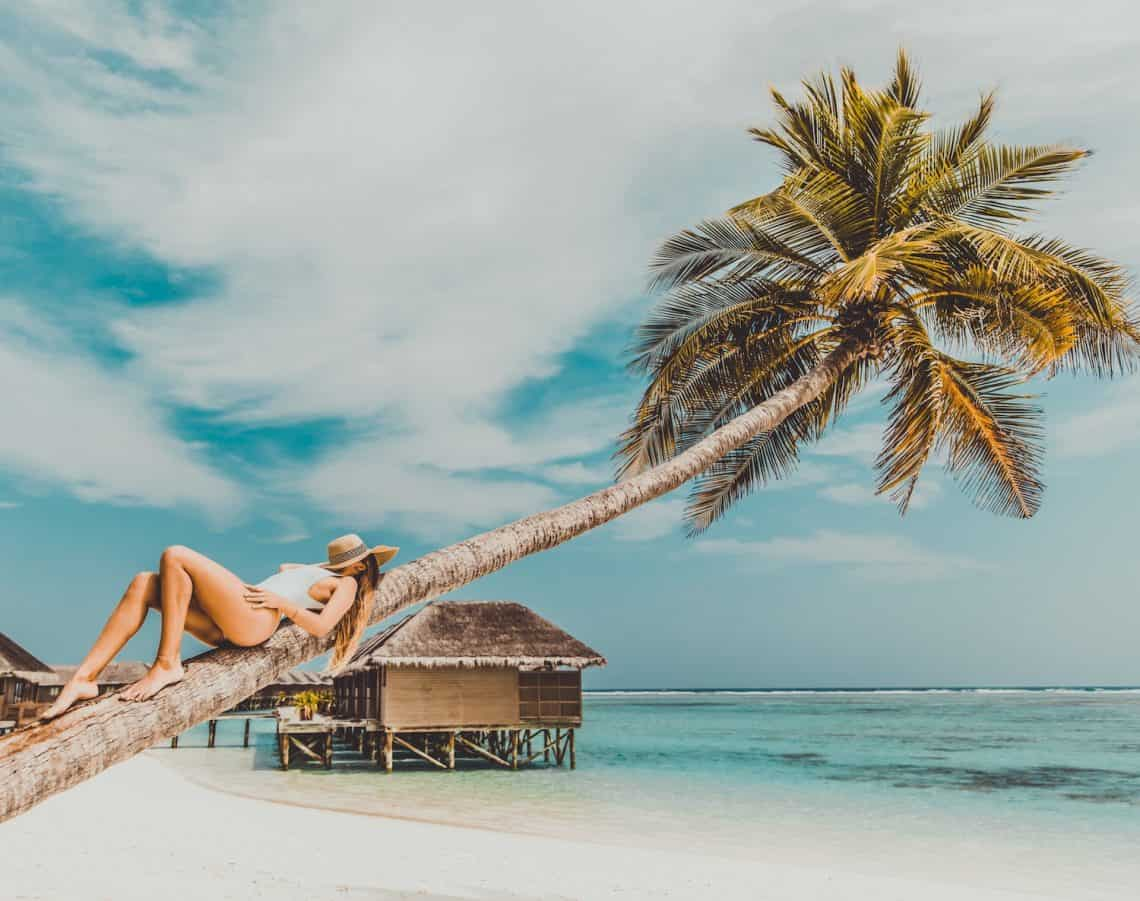 woman lying on coconut tree trunk at beach tropical vacation